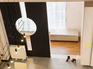户玄关左侧是落地窗,朦胧的窗纱、软软的长凳、温馨的木地板给人放松舒适的回家氛围,从素净的柜门的质感和金属边框来点亮前方转角处理的鞋柜区域,右侧是半通透的钢板夹木头隔断